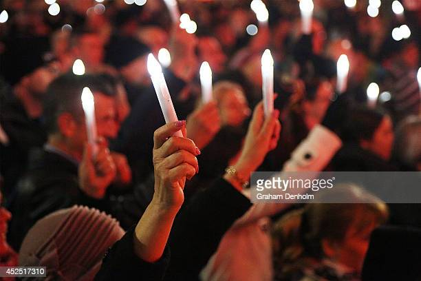 Members of the public hold candles to mourn the victims of HIV/AIDS and the victims of flight MH17 during a candlelight vigil at Federation Square on...
