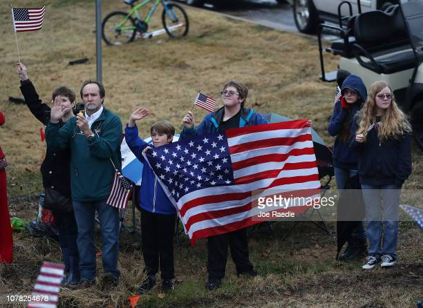Members of the public hold signs and flags as the train carrying former President George HW Bush to his final resting place passes by on December 6...