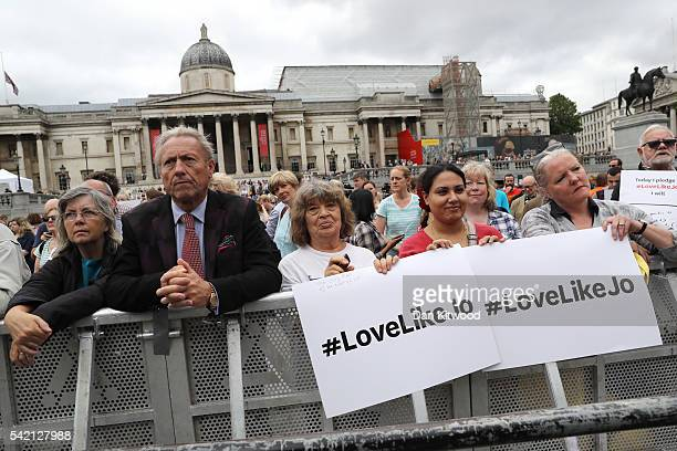 """Members of the public hold signs saying """"#LoveLikeJo"""" as they attend a memorial event for murdered Labour MP Jo Cox at Trafalger Square on June 22,..."""