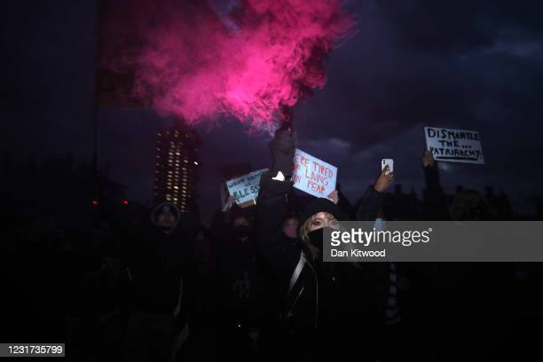 Members of the public hold up signs and smoke flares during a protest in Parliament Square against the The Police, Crime, Sentencing and Courts Bill...