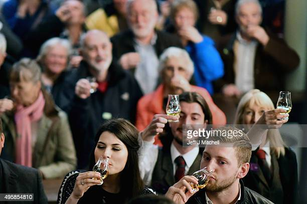 Members of the public hold up whisky glasses at Glenturret Distillery in an attempt to set a record for the most people to raise a dram toast at the...