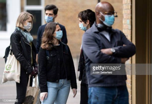 Members of the public in face masks queue 2 meters apart outside a shop in East London on April 25, 2020 in London, England. The British government...