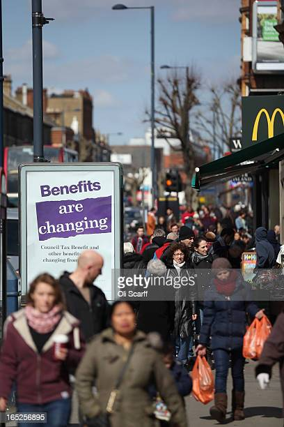 Members of the public in North London walk past a poster informing of changes to the benefits and tax system that have come into force yesterday on...