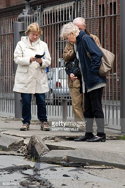 Members of the public inspect the damage to the road on the Wellington water front after a 78 earthquake centred in the South Island in Wellington on...