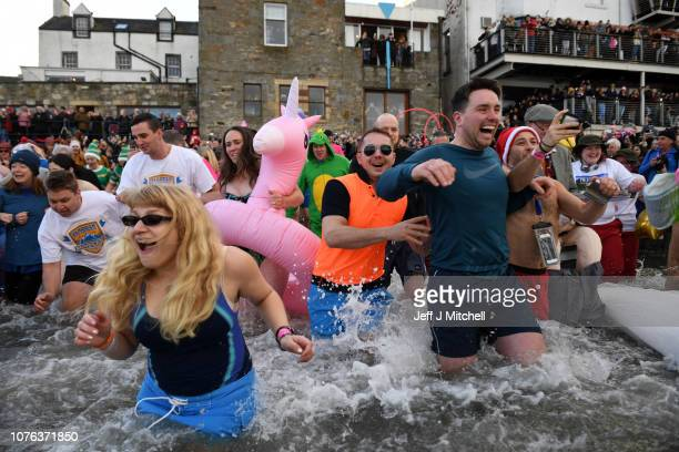 Members of the public join New Year swimmers, many in costume, in front of the Forth Rail Bridge during the annual Loony Dook Swim in the River Forth...