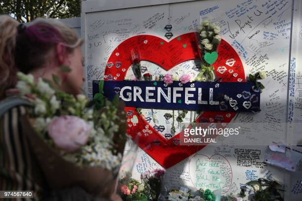 Members of the public lay tributes at a memorial at the base of the Grenfell Tower as part of commemorations on the first anniversary of the Grenfell...