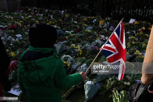 Members of the public leave floral tributes to Prince Philip, Duke Of Edinburgh who died at age 99, outside of Windsor Castle on April 11, 2021 in...