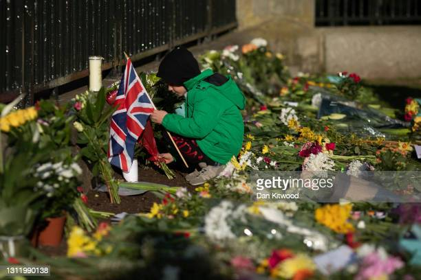 Members of the public leave floral tributes to Prince Philip, Duke Of Edinburgh who died at age 99 outside of Windsor Castle on April 11, 2021 in...