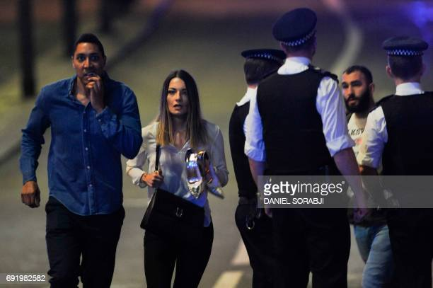 Members of the public leave the scene of a terror attack on London Bridge in central London on June 3 2017 Armed police opened fire during what they...
