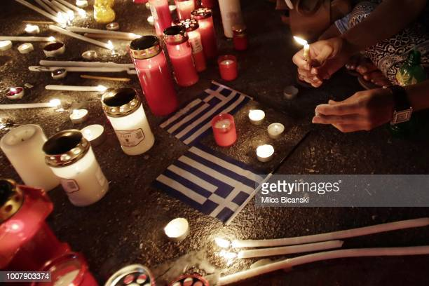 Members of the public light candles outside the Greek Parliament to commemorate the victims of the country's worst ever wildfires on July 30 2018 in...
