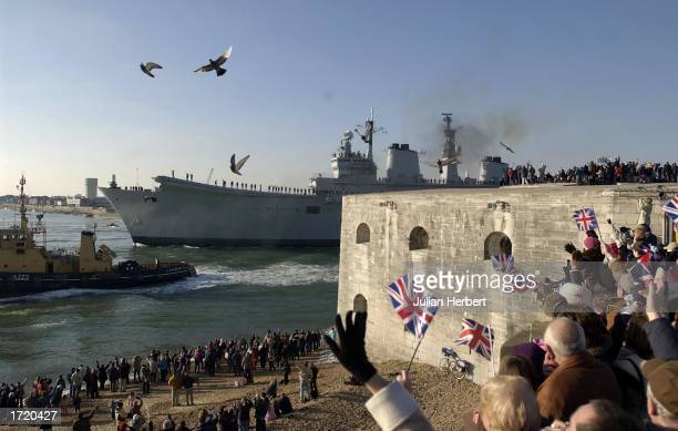 Members of the public line the shore as the aircraft carrier HMS Ark Royal leaves her base January 11 in Portsmouth England were she will lead a...