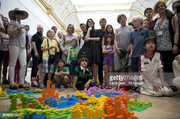Members of the public listen as the team from Zaha Hadid Architects explain their design in the UK's first Lego battle inside the Royal Academy's...