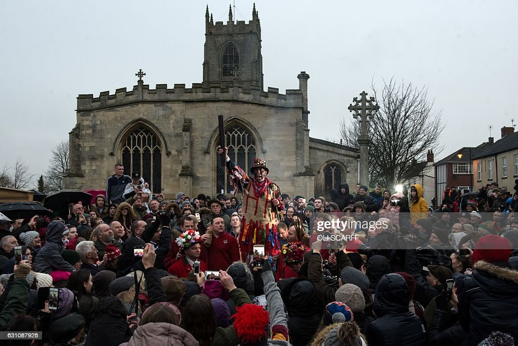 Members of the public listen to a man dressed as the 'Fool' as he delivers a speech before the annual game of Haxey Hood in the village of Haxey in North Lincolnshire, northern England on January 6, 2017. The Haxey Hood game, which has few rules, involves an unlimited number of participants attempting to carry a leather tube to one of four local pubs. The Haxey Hood game is reported to date back to the 14th century. / AFP / OLI