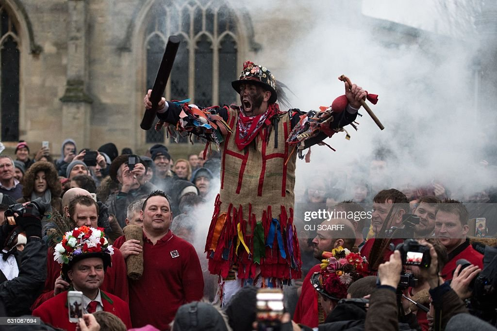 Members of the public listen to a man dressed as the 'Fool' deliver a speech as he is smoked, before the annual game of Haxey Hood in the village of Haxey in North Lincolnshire, northern England on January 6, 2017. The Haxey Hood game, which has few rules, involves an unlimited number of participants attempting to carry a leather tube to one of four local pubs. The Haxey Hood game is reported to date back to the 14th century. / AFP / OLI