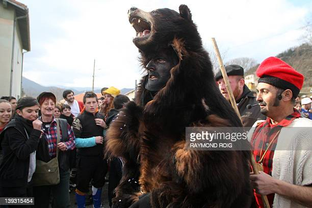 Members of the public look at a man, dressed up with a real bearskin , parading on February 19, 2012 in the streets of the catalan village of...