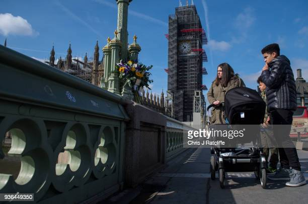 Members of the public look at floral tributes for victims on Westminster Bridge on the first anniversary of the Westminster Bridge terror attack on...