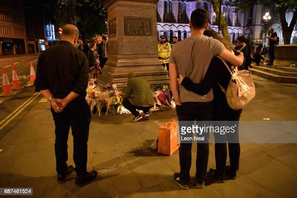 Members of the public look at some of the floral tributes following an evening vigil outside the Town Hall on May 23 2017 in Manchester England An...