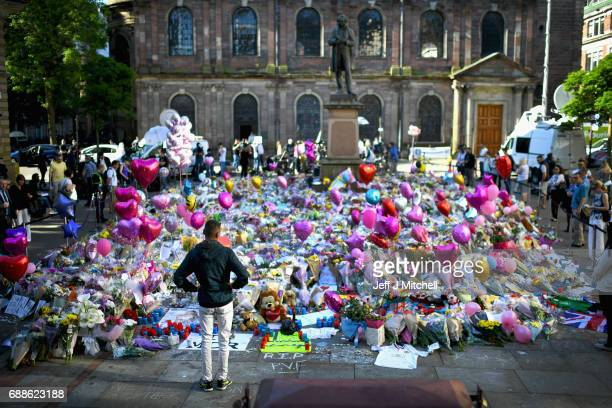 Members of the public look at tributes left in St Ann's Square for the people who died in Monday's terror attack at the Manchester Arena on May 26...