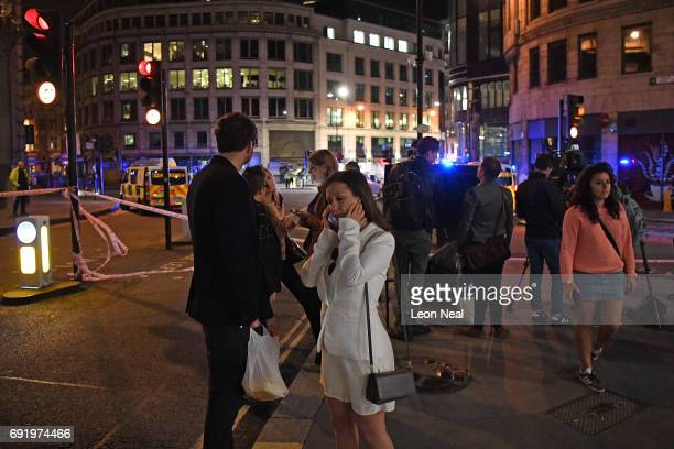 Members of the public look on as a police close off the area by Monument station on June 3 2017 in London England Police have responded to reports of...