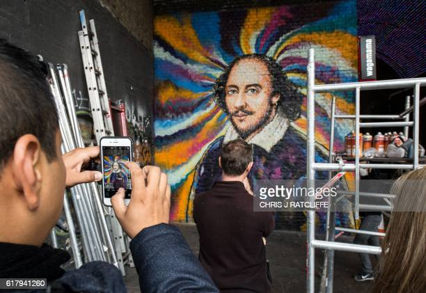 Members of the public look on as graffiti artist James Cochran aka Jimmy C paints a mural of William Shakespeare on Clink Street near the...