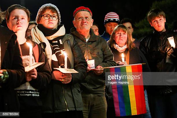 Members of the public look on during a candlelight vigil for the victims of the Pulse Nightclub shooting in Orlando Florida at Frank Kitts Park on...