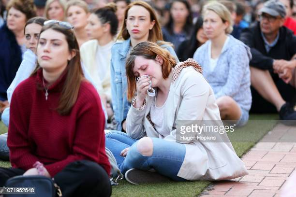 Members of the public look on during a vigil for British backpacker Grace Millane at Civic Square on December 12 2018 in Wellington New Zealand The...