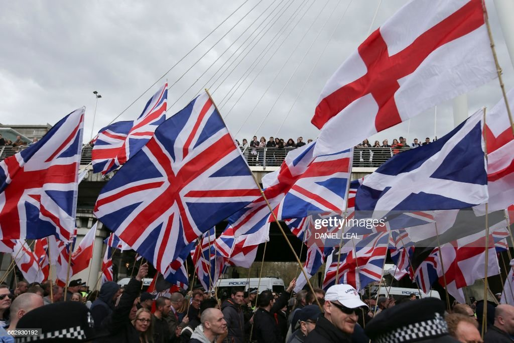 Members of the public look on from a bridge at people holding flags taking part in a march organised by the far-right group Britain First in central London on April 1, 2017 following the March 22 terror attack on the British parliament. Members of the Britain First group and the English Defence League rallied in central London in on seperate marches entitled a 'March Against Terrorism' and 'We Are Not Afriad' following the terror attack on Westminster Bridge and the British Parliament on March 22 which killed four people. The marches were opposed by the Unite Against Fascism organisation who held a static demonstration against the other groups. / AFP PHOTO / Daniel LEAL