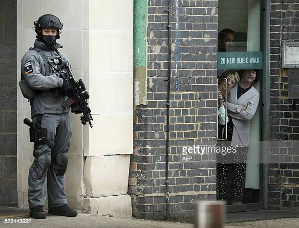 Members of the public look out from behind a glass door as an armed British police officer secures the area before the arrival of US President Barack...
