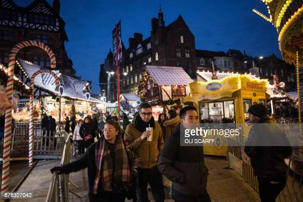 Members of the public make their way through a temporary seasonal Christmas market in Nottingham city centre in Nottingham, central England on...