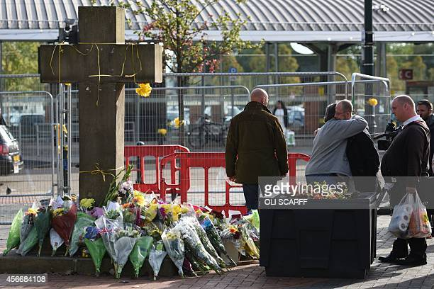 Members of the public observe the floral tributes at the base of the Eccles Cross for murdered aid worker Alan Henning in Eccles north west England...