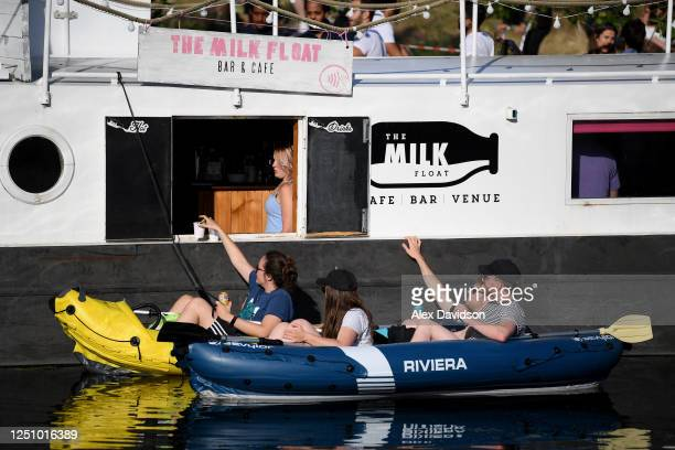 Members of the public on Kayak's are served at a riverside bar on June 20 2020 in London England