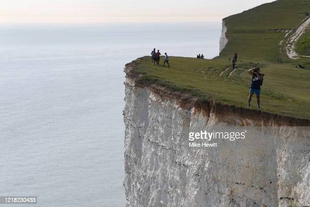 Members of the public out enjoying the sunshine and scenery at Beachy Head on April 11, 2020 in Eastbourne, United Kingdom. The Coronavirus pandemic...