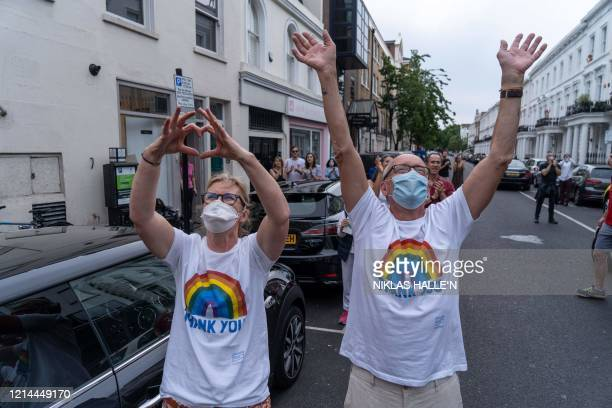 """Members of the public participate in a national """"clap for carers"""" to show thanks for the work of Britain's NHS workers and other frontline medical..."""