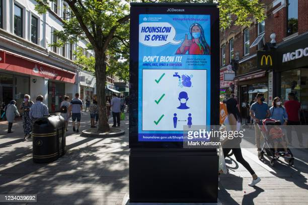 Members of the public pass a London Borough of Hounslow Covid-19 public information display urging residents to take precautions to minimise the...