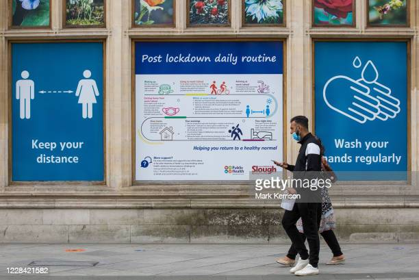 Members of the public pass COVID-19 public information displays on 9 September 2020 in Slough, United Kingdom. The UK government will implement...