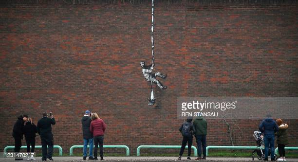 Members of the public pause to look at an artwork bearing the hallmarks of street artist Banksy on the side of Reading Prison in Reading, west of...