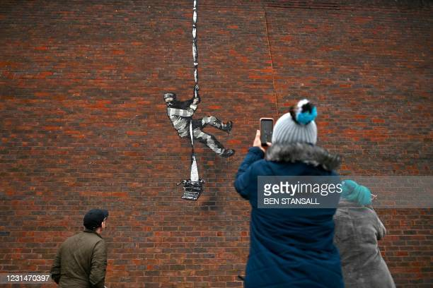Members of the public pause to take photographs of an artwork bearing the hallmarks of street artist Banksy on the side of Reading Prison in Reading,...