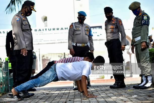 Members of the public perform push-ups as punishment for not wearing face masks amid the Covid-19 coronavirus pandemic in Banda Aceh on November 10,...