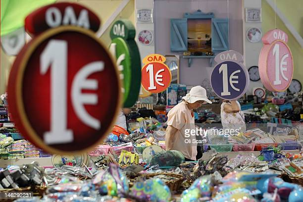 Members of the public peruse items for sale in a discount '1 Euro' shop on June 13 2012 in Athens Greece The Greek electorate are due to go to the...