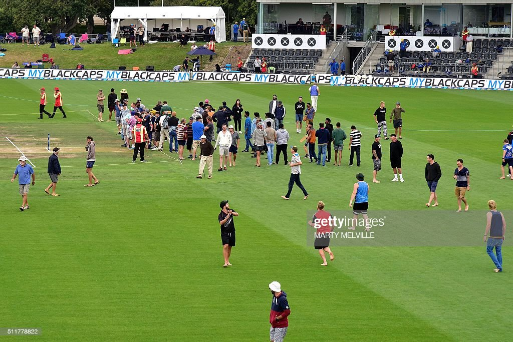 Members of the public play cricket and inspect the wicket during the lunch break on day four of the second cricket Test match between New Zealand and Australia at the Hagley Park in Christchurch on February 23, 2016. AFP PHOTO / MARTY MELVILLE / AFP / Marty Melville