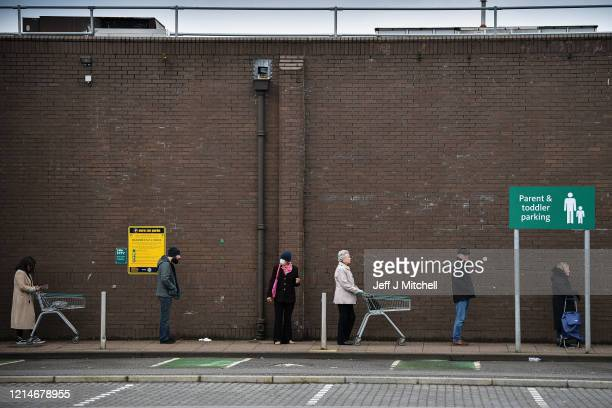Members of the public practice social distancing as they shop for food in Partick amid the coronavirus outbreak on March 25, 2020 in Glasgow,...