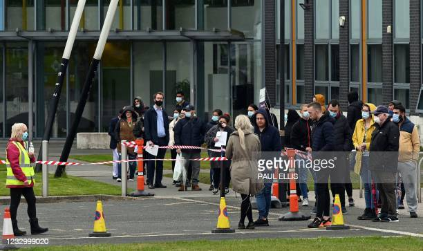 Members of the public queue for vaccinations outside of a temporary vaccination centre at the Essa academy in Bolton, northwest England on May 20,...