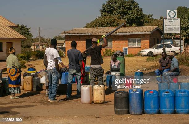 Members of the public queue for water at a borehole in Tafara on August 1, 2019 in Harare, Zimbabwe. Zimbabwe is facing an acute water shortage after...