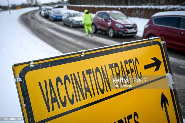 Members of the public queue in their cars as they wait to receive a vaccine for COVID-19 on the opening day of NHS Lothian's first drive through mass...