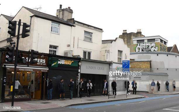 Members of the public queue outside a Barbers in Clapham on July 04 2020 in London United Kingdom Hairdressing Salons reopen today having been closed...