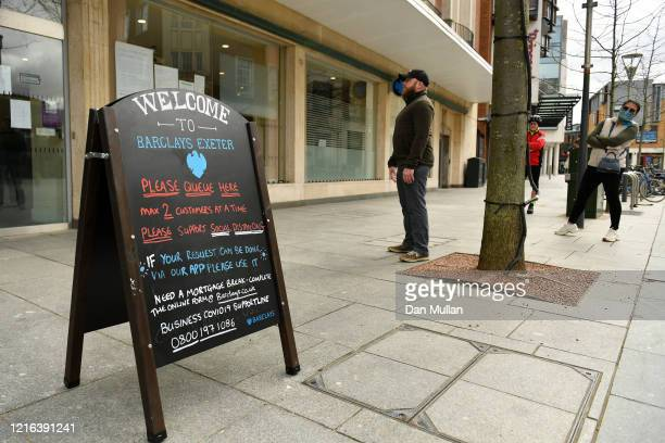 Members of the public queue outside a Barclays bank in the city centre on April 02 2020 in Exeter England The Coronavirus pandemic has spread to many...