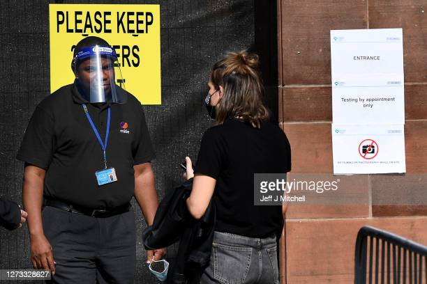 Members of the public queue to enter a walk through coronavirus test centre at Glasgow Caledonian University on September 18, 2020 in Glasgow,...