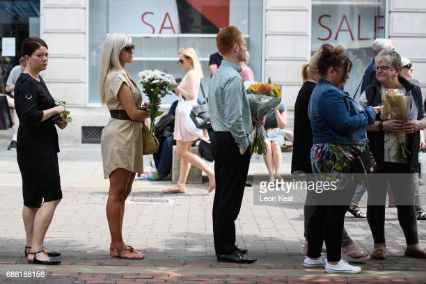 Members of the public queue to lay their floral tributes following a national minute's silence in remembrance of all those who lost their lives in...