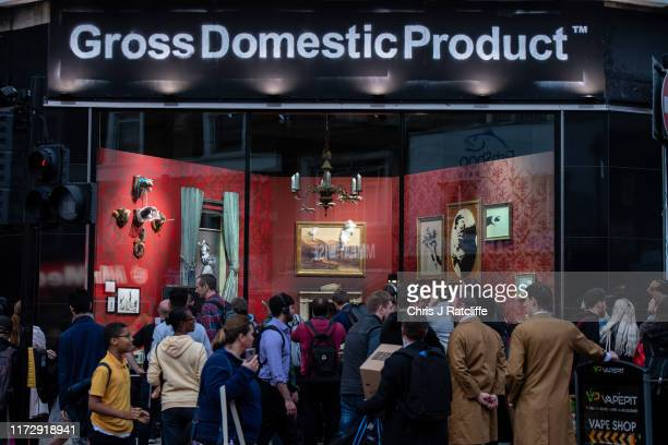 Members of the public queue to look at a new installation by elusive artist Banksy on October 1, 2019 in Croydon, England. The shop names 'Gross...