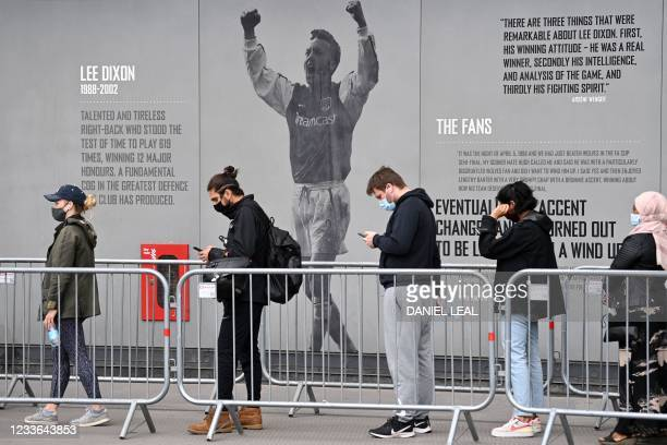 Members of the public queue to receive a dose of a Covid-19 vaccine outside a temporary vaccination centre set up a the Emirates Stadium, home to...